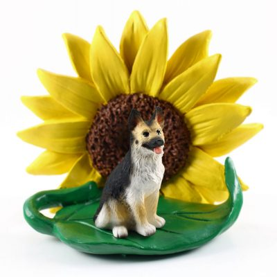 German Shepherd Black/Tan Figurine Sitting on a Green Leaf in Front of a Yellow Sunflower