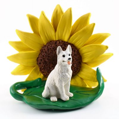 German Shepherd White Figurine Sitting on a Green Leaf in Front of a Yellow Sunflower