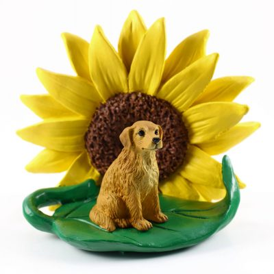 Golden Retriever Figurine Sitting on a Green Leaf in Front of a Yellow Sunflower