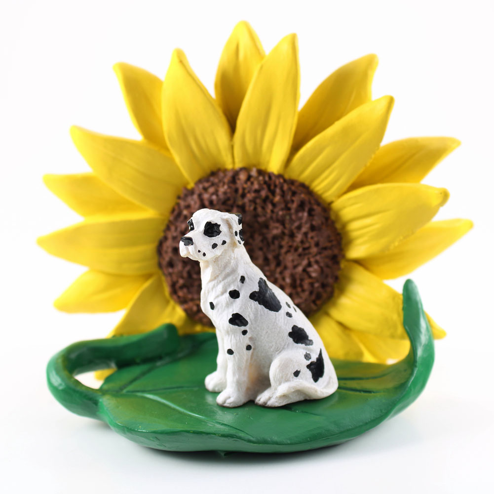 Great Dane Harlequin Uncropped Figurine Sitting on a Green Leaf in Front of a Yellow Sunflower