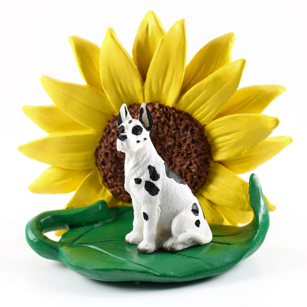 Great Dane Harlequin Figurine Sitting on a Green Leaf in Front of a Yellow Sunflower