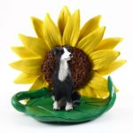 Greyhound Black/White Figurine Sitting on a Green Leaf in Front of a Yellow Sunflower