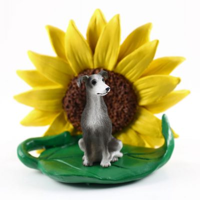 Greyhound Gray/White Figurine Sitting on a Green Leaf in Front of a Yellow Sunflower