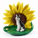 Husky Black/White Blue Eyes Figurine Sitting on a Green Leaf in Front of a Yellow Sunflower