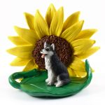 Husky Black/White Brown Eyes Figurine Sitting on a Green Leaf in Front of a Yellow Sunflower