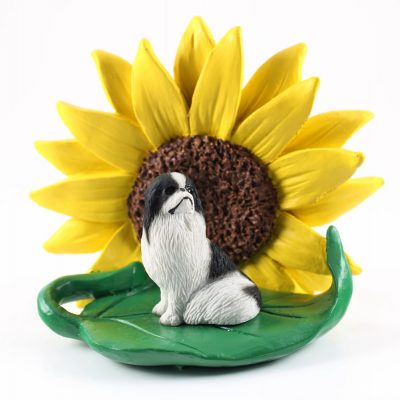 Japanese Chin Black Figurine Sitting on a Green Leaf in Front of a Yellow Sunflower