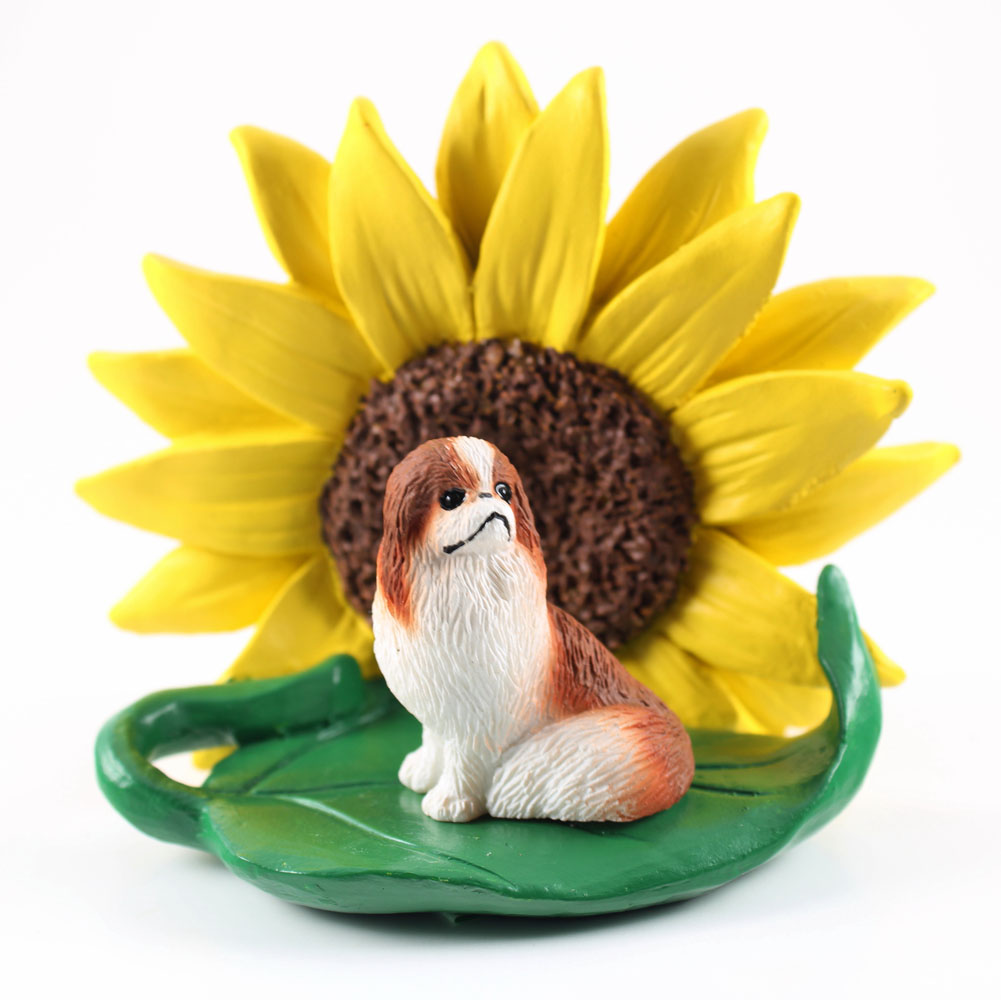 Japanese Chin Red Figurine Sitting on a Green Leaf in Front of a Yellow Sunflower
