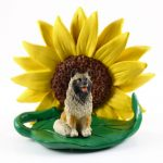 Keeshond Figurine Sitting on a Green Leaf in Front of a Yellow Sunflower