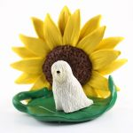 Komondor Figurine Sitting on a Green Leaf in Front of a Yellow Sunflower
