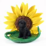 Labradoodle Black Figurine Sitting on a Green Leaf in Front of a Yellow Sunflower