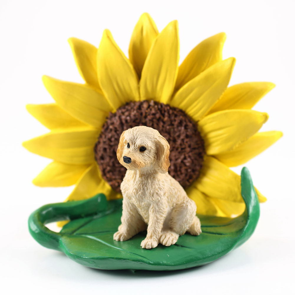 Labradoodle Blonde Figurine Sitting on a Green Leaf in Front of a Yellow Sunflower