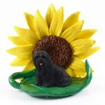 Llhasa Apso Black Figurine Sitting on a Green Leaf in Front of a Yellow Sunflower