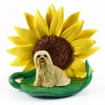 Llhasa Apso Blonde Figurine Sitting on a Green Leaf in Front of a Yellow Sunflower