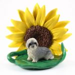 Llhasa Apso Gray Puppy Cut Figurine Sitting on a Green Leaf in Front of a Yellow Sunflower