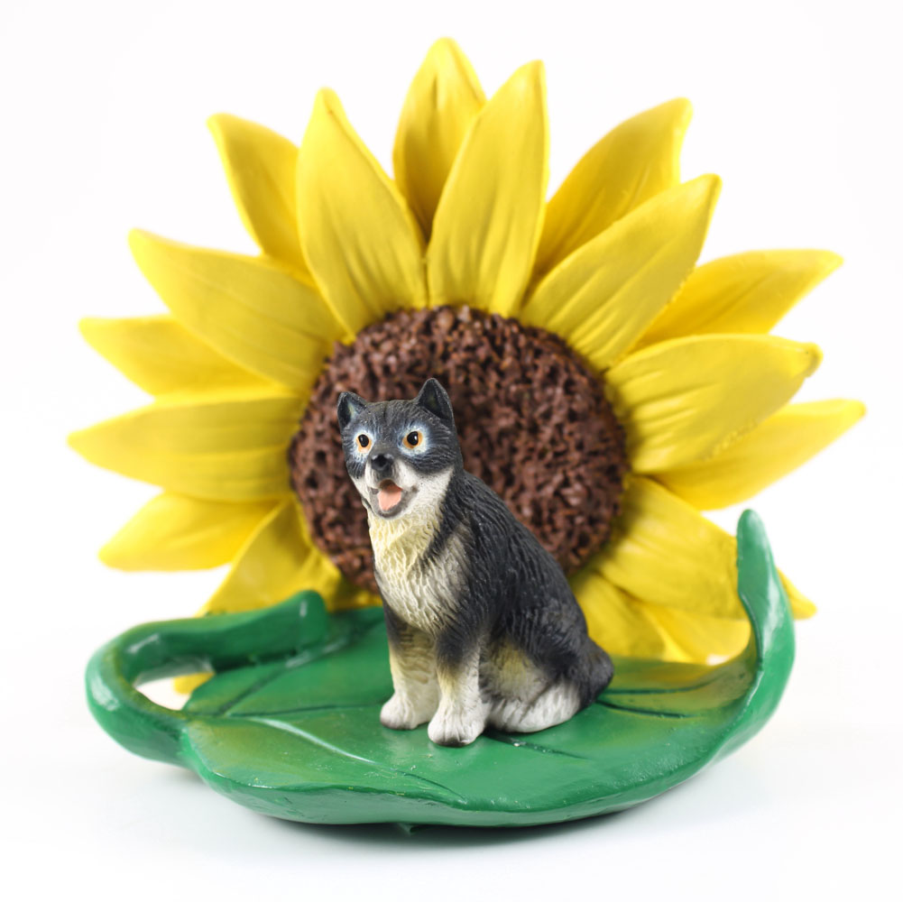 Malamute Figurine Sitting on a Green Leaf in Front of a Yellow Sunflower