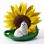Maltese Figurine Sitting on a Green Leaf in Front of a Yellow Sunflower
