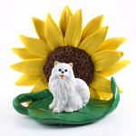 Mini American Eskimo Figurine Sitting on a Green Leaf in Front of a Yellow Sunflower