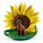 Mini Pinscher Red Figurine Sitting on a Green Leaf in Front of a Yellow Sunflower