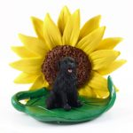 Newfoundland Figurine Sitting on a Green Leaf in Front of a Yellow Sunflower
