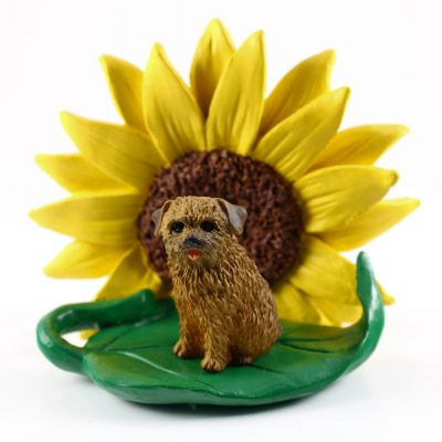 Norfolk Terrier Figurine Sitting on a Green Leaf in Front of a Yellow Sunflower