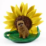 Norwich Terrier Figurine Sitting on a Green Leaf in Front of a Yellow Sunflower