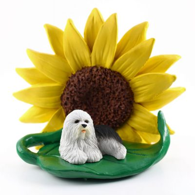 Old English Sheepdog Figurine Sitting on a Green Leaf in Front of a Yellow Sunflower