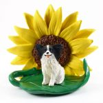 Papillon Black Figurine Sitting on a Green Leaf in Front of a Yellow Sunflower