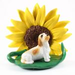Petit Basset Griffon Vendeen Figurine Sitting on a Green Leaf in Front of a Yellow Sunflower