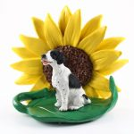 Pointer Black Figurine Sitting on a Green Leaf in Front of a Yellow Sunflower