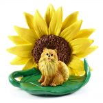 Pomeranian Red Figurine Sitting on a Green Leaf in Front of a Yellow Sunflower