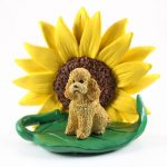 Poodle Apricot Sport Cut Figurine Sitting on a Green Leaf in Front of a Yellow Sunflower