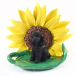 Poodle Black Sport Cut Figurine Sitting on a Green Leaf in Front of a Yellow Sunflower
