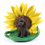 Poodle Chocolate Sport Cut Figurine Sitting on a Green Leaf in Front of a Yellow Sunflower