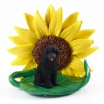 Portuguese Water Dog Figurine Sitting on a Green Leaf in Front of a Yellow Sunflower