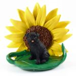 Pug Black Figurine Sitting on a Green Leaf in Front of a Yellow Sunflower