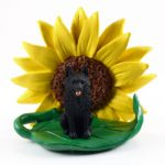 Schipperke Figurine Sitting on a Green Leaf in Front of a Yellow Sunflower