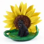 Schnauzer Black Figurine Sitting on a Green Leaf in Front of a Yellow Sunflower