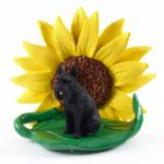 Schnauzer Black Giant Figurine Sitting on a Green Leaf in Front of a Yellow Sunflower