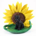 Schnauzer Black Uncropped Figurine Sitting on a Green Leaf in Front of a Yellow Sunflower