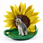 Schnauzer Gray Giant Figurine Sitting on a Green Leaf in Front of a Yellow Sunflower