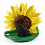 Scottish Terrier Figurine Sitting on a Green Leaf in Front of a Yellow Sunflower