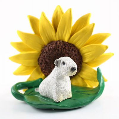 Sealyham Terrier Figurine Sitting on a Green Leaf in Front of a Yellow Sunflower