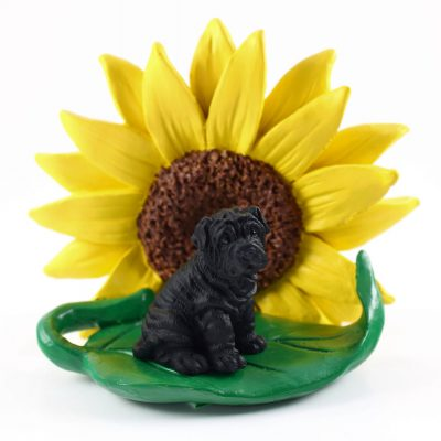 Shar Pei Black Figurine Sitting on a Green Leaf in Front of a Yellow Sunflower