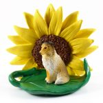 Sheltie Sable Figurine Sitting on a Green Leaf in Front of a Yellow Sunflower
