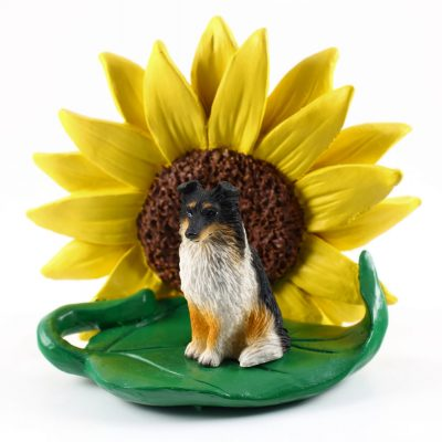 Sheltie Tri Color Figurine Sitting on a Green Leaf in Front of a Yellow Sunflower