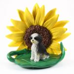 Shih Tzu Black/White Puppy Cut Figurine Sitting on a Green Leaf in Front of a Yellow Sunflower