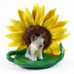 Skye Terrier Figurine Sitting on a Green Leaf in Front of a Yellow Sunflower
