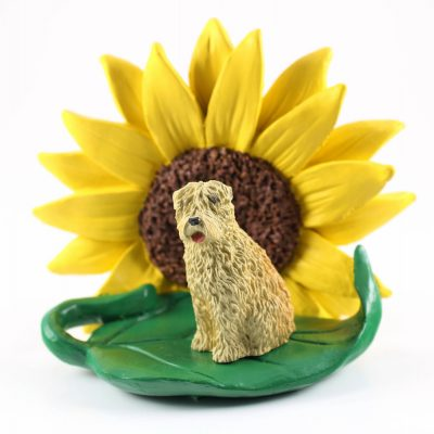 Soft Coated Wheaten Figurine Sitting on a Green Leaf in Front of a Yellow Sunflower