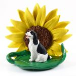 Springer Spaniel Black Figurine Sitting on a Green Leaf in Front of a Yellow Sunflower