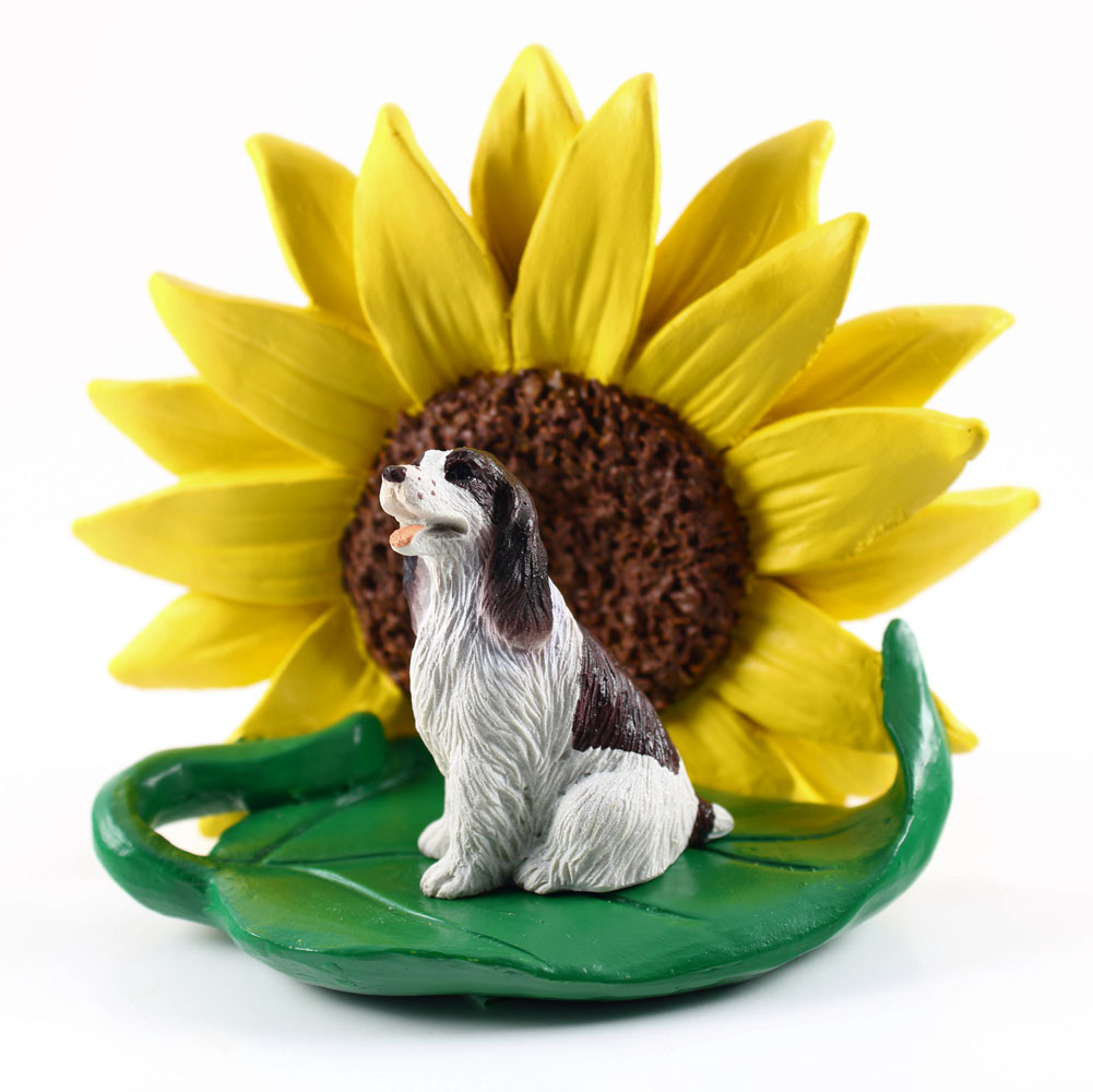 Springer Spaniel Brown Figurine Sitting on a Green Leaf in Front of a Yellow Sunflower